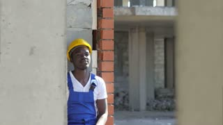 Young afro-american construction worker takes a break during work