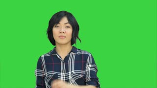 Young asian woman smiling and dancing on a Green Screen, Chroma Key