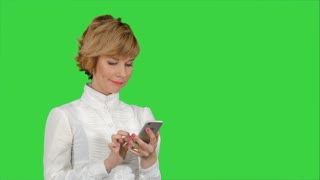 Young attractive woman works on smartphone and smiles on a Green Screen, Chroma Key