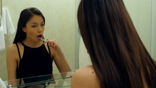 Young beautiful caucasian brunette woman brushing teeth and smiling in the mirror