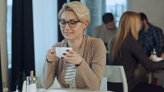 Young beautiful woman drinking coffee at cafe bar