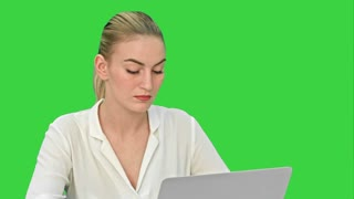 Young blonde businesswoman working on laptop computer on a Green Screen, Chroma Key