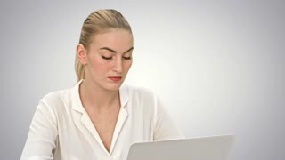 Young blonde businesswoman working on laptop computer on white background
