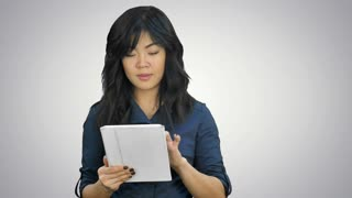Young business woman with tablet computer presenting project looking at camera on white background
