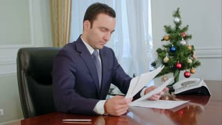 Young businessman reading documents and signing it by the desk near New Year Tree
