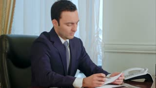 Young businessman reading paperwork at desk in office and smiling