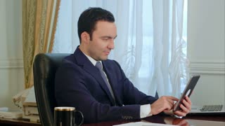 Young businessman using modern digital tablet searching the Internet