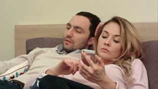 Young couple fighting, arguing in bed at night because woman texting someone using smartphone