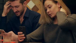 Young couple using cell phones and taking funnie selfie photo sitting in cafe