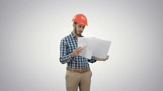 Young engineer in helmet checking construction plan on white background