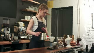 Young female barista in trendy modern cafe coffee shop pours boiling water over coffee grounds making a pour over drip coffee