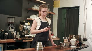 Young female coffe shop owner have a phone call using smartphone in cafeteria