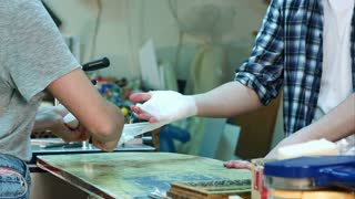 Young female colleague carefully bandaging worker injured hand after accident in workshop