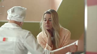 Young female doctor with female patient talking in hospital room
