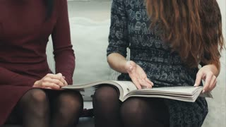 Young female hands flipping through a fashion magazine sitting on a sofa