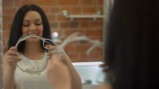 Young lovely girl tries on hair accessory looking in a mirror and laughing