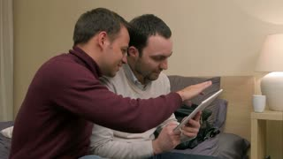 Young male friends and sitting on the sofa and using tablet, duscussing something and laughing