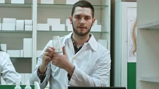 Young malepharmacist holding a white blank bottle of pills, promoting medicine, while his colleague working