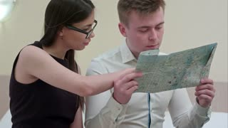 Young man and woman checking map, talking, planning family vacation