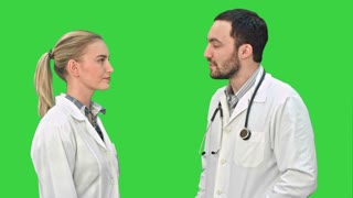 Young man doctor and beautiful nurse shaking hands after successful operation and looking at camera on a Green Screen, Chroma Key