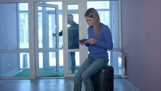 Young man entering the doors and talking to smiling woman with tablet sitting on suitcase
