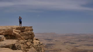 Young man standing on cliff edge and taking pictures of the desert on his phone