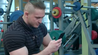 Young man using phone while having exercise break in the gym