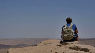 Young man with backpack sitting on cliff's edge and enjoying the desert view