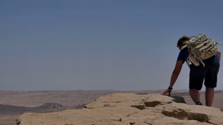 Young man with backpack sitting on cliff's edge and looking at the desert
