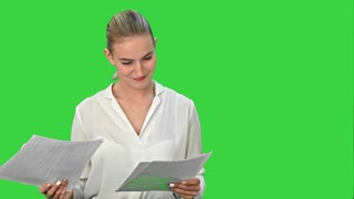 Young pretty businsswoman throws paper document pages on a Green Screen, Chroma Key