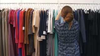 Young shop owner looking at trendy clothes hanged on rail inside the clothes store