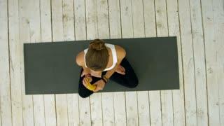 Young woman eating banana after yoga class