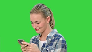 Young woman smiling while texting a message via cell phone on a Green Screen, Chroma Key