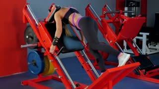 Young woman training buttock using gym equipment