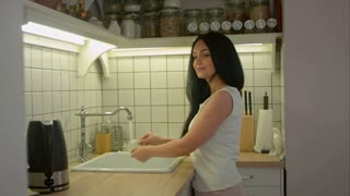 Young woman washing dirty dishes with soap and talking to someone in home kitchen