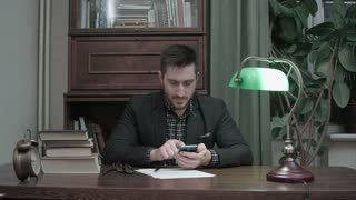 Young writer at his desk happily messaging on mobile phone