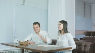 Waiter bringing menu to young couple sitting at the table in a restaurant