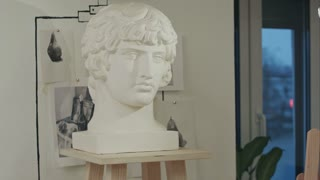 White plaster bust sculpture portrait of a young man in art studio