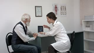 Woman doctor talking with senior patient in the office and showing him tablet with mri.