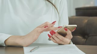 Woman hands using cell phone in restaurant