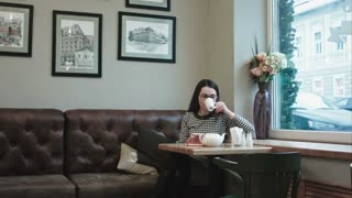 Woman in the cafe discuss quality of tea in kettle with bearded waiter