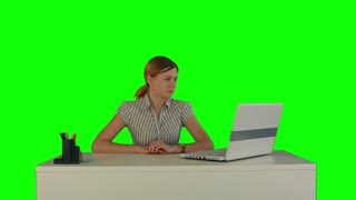 Woman is working on the laptop on a Green Screen