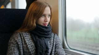 Woman look in window inside train, think and smile