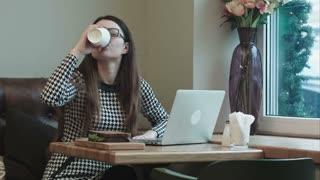 Woman on lunch break in cafe drinks coffee use laptop
