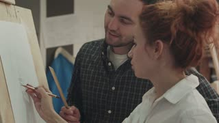 Woman painter teaching young man how to draw face