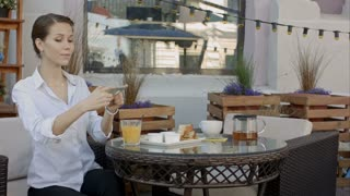 Woman photographing food by smartphone in cafe