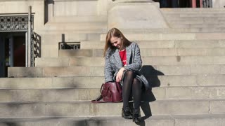 Woman searching something in her hand bag sitting on stairs of building