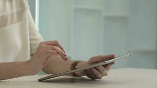 Woman sitting in office table and touch tablet