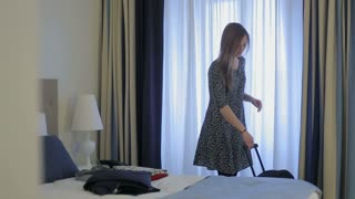 woman tourist packing a suitcase in hotel