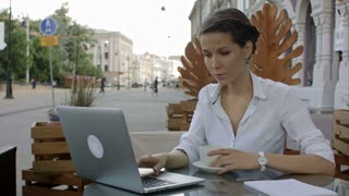 Woman using laptop and free wifi at outdoor cafe